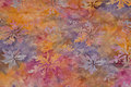 Batique-cotton in orange and light-purple with dispersed leaves.