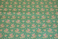Jade-green cotton with small soft red flowers.