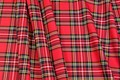 This tartan fabric is of a light quality with a strong red base and black, white and yellow lines. Rectangular areas are ca. 12 cm diameter.
