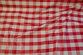 Red and white checkered coated fabric with 3 x 3 cm checkers.