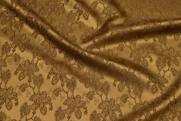 Brass-colored jacquard-satin with flower pattern