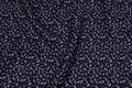 Polyester mousselin in black with sand-colored pattern