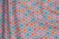 White cotton with small flowers in grey and orange and turqoise and soft red