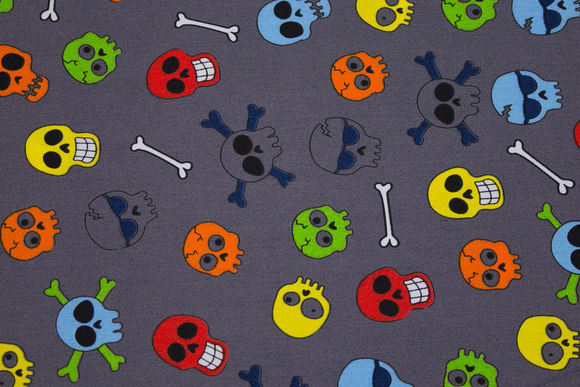 Grey-brown, woven cotton with colorful skulls and bones