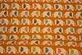 Organic orange cotton with elephants on a row.