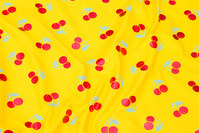 Yellow cotton-jersey with shiny, red cherries