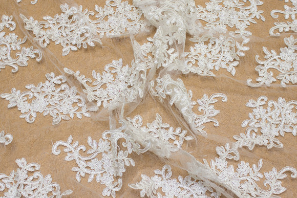 Beautiful creme-colored lace on tulle base with scallop edges