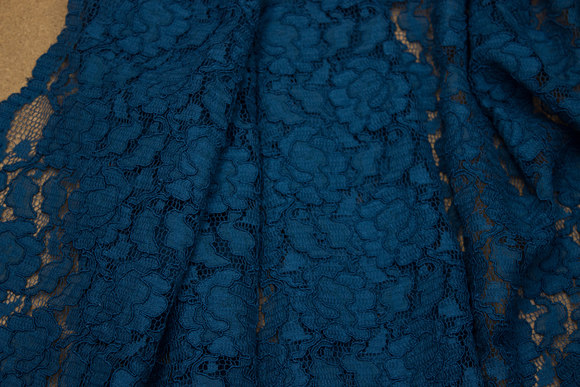 Firm, petrol-colored dress-lace-fabric with scallops in both sides