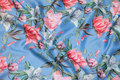 Light blue, lightweight polyester-satin with coral-colored flowers.