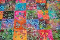 Batique-patchwork sewn in 10 cm squares in red, orange, pink and blue nuances