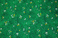 Green patchwork-cotton with grass, small daisies.