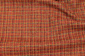 Ruggedly woven opholstry fabric in red and green nuances.