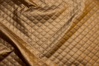 Surface-textured quilt in gold-cobber-colored