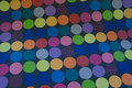 Multicolored dots on coated textile-table-cloth.