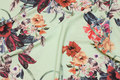 Light green lightweight polyestercrepe with flowers in red nuances
